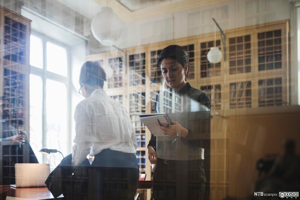 To kvinner reiser seg og sjekker notatblokka. Bilde.