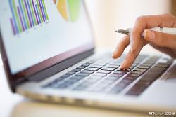 En hånd som holder en penn, trykker på tastaturet på en bærbar PC. På skjermen er det ulike diagrammer. Foto.