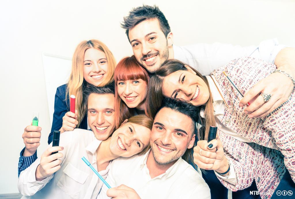 Smilende mennesker med markeringstusjer og penn. Foto.