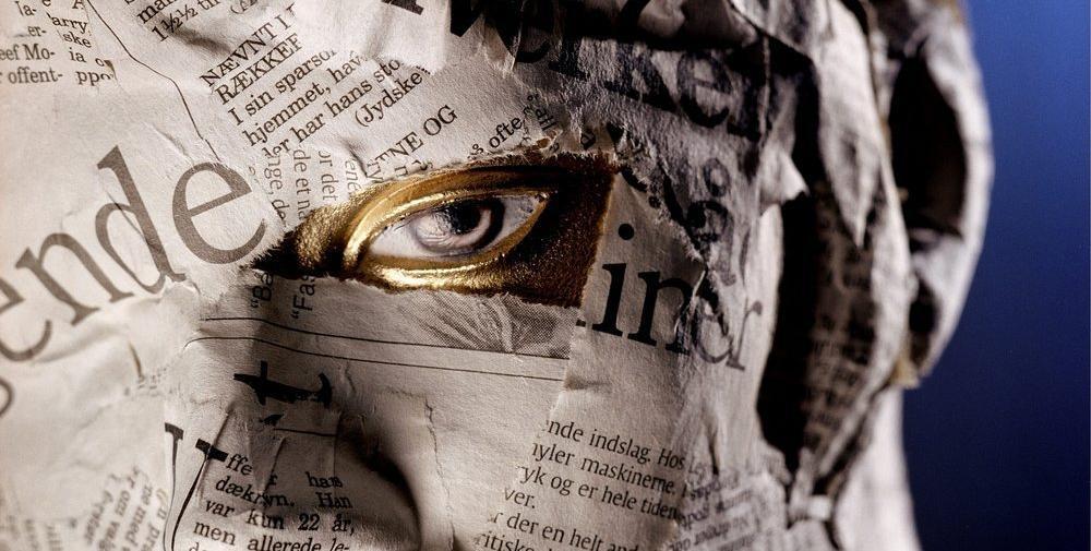 Et ansikt hvor huden er dekket med avispapir, bortsett fra ett øye. Huden rundt øyet er gullfarget. Foto.