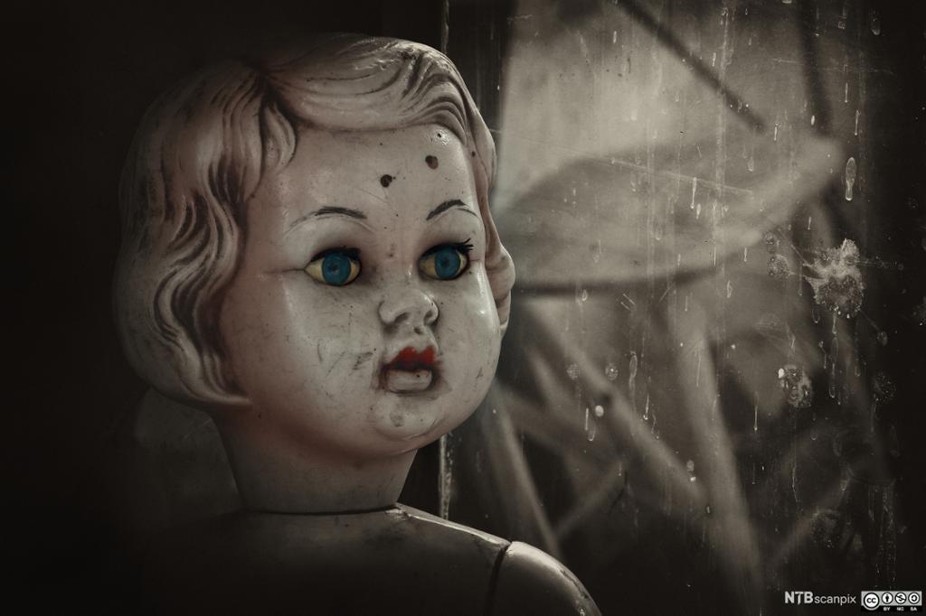 Gammel dukke med grønn øyne og hull i panna. Foto.