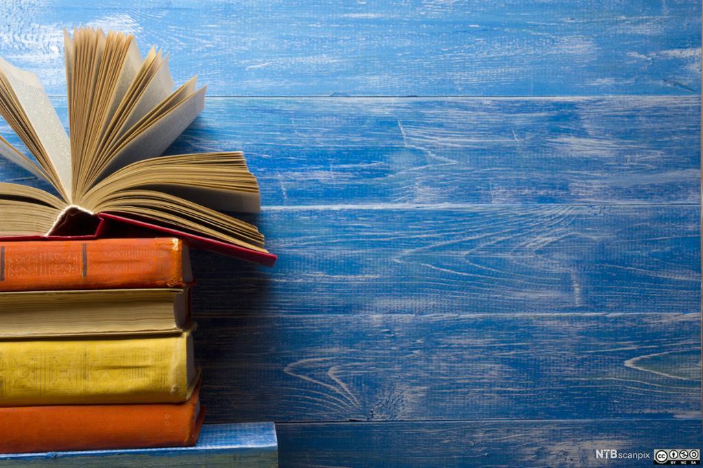 En stabel med bøker på blå bakgrunn.