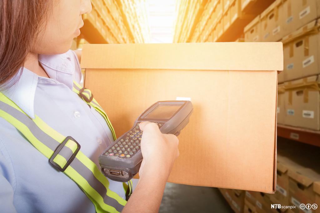 Nærbilde av person som skanner en boks med strekkodeleser. Foto.