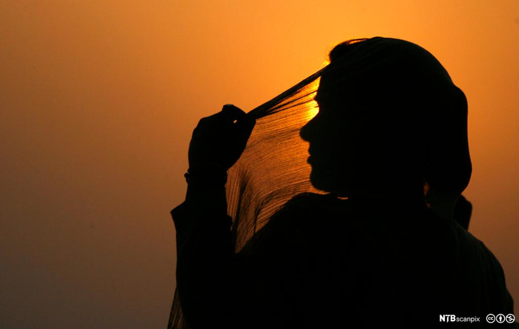 Indian woman adjusts her scarf as the sun sets