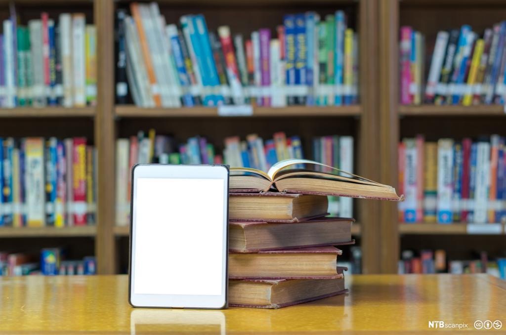 Bøker og nettbrett på et bibliotek. Bilde.
