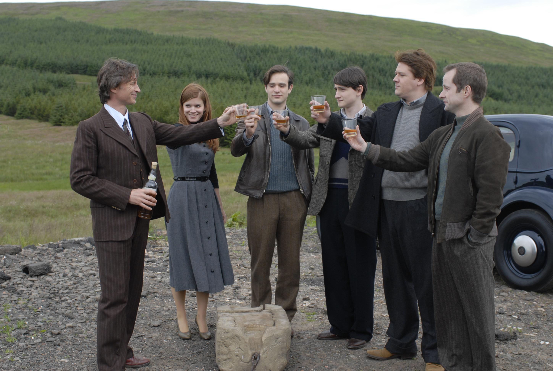 En gjeng skåler i whisky mens de står rundt en stein. Foto