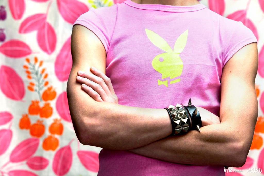 Mann med rosa t-skjorte og svart lærarmbånd med pigger. Foto.