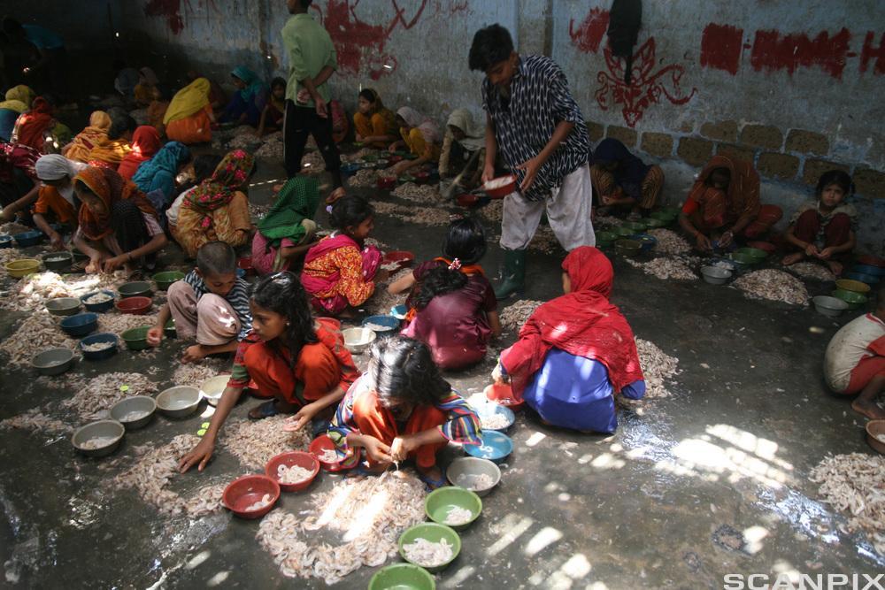 Barn i fargerike klær sitter på gulvet. Foto.