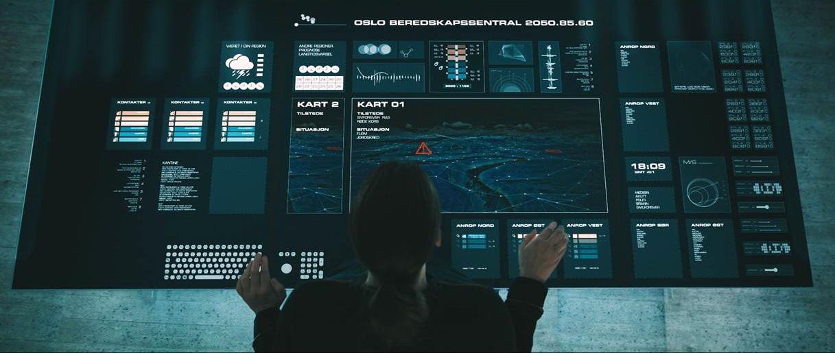Kvinne sitter foran stort kontrollpanel med berøringsskjerm. Foto.