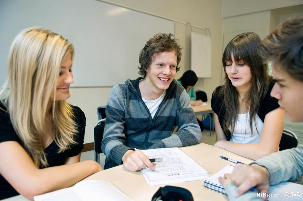 Elever sitter rundt pult i klasserom. Foto.