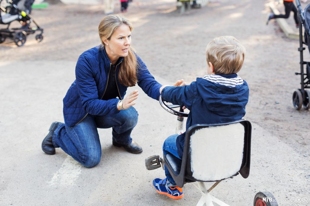 En voksen kvinne sitter på huk foran en gutt på trehjulssykkel. Hun holder opp hendene mot gutten og ser streng ut. Foto.
