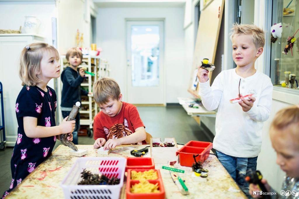 Flere barn rundt et bord. De bruker ulike materialer til å forme med. Foto.