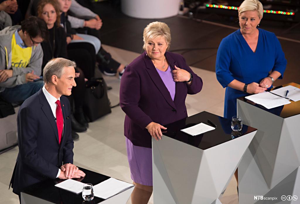 Jonas Gahr Støre fra Arbeiderpartiet, Erna Solberg fra Høyre og Siv Jensen fra Fremskrittspartiet står bak hver sin talerstol og debatterer med tilhørere i bakgrunnen. Foto.