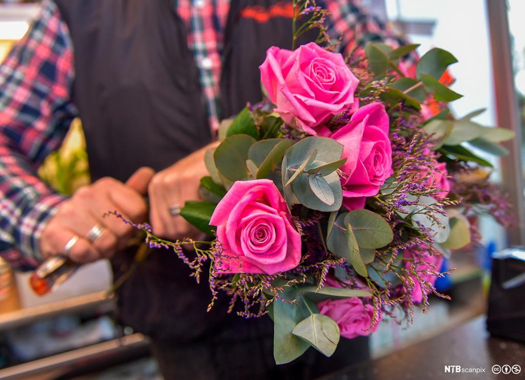 En blomsterdekoratør setter sammen en bukett. Foto.