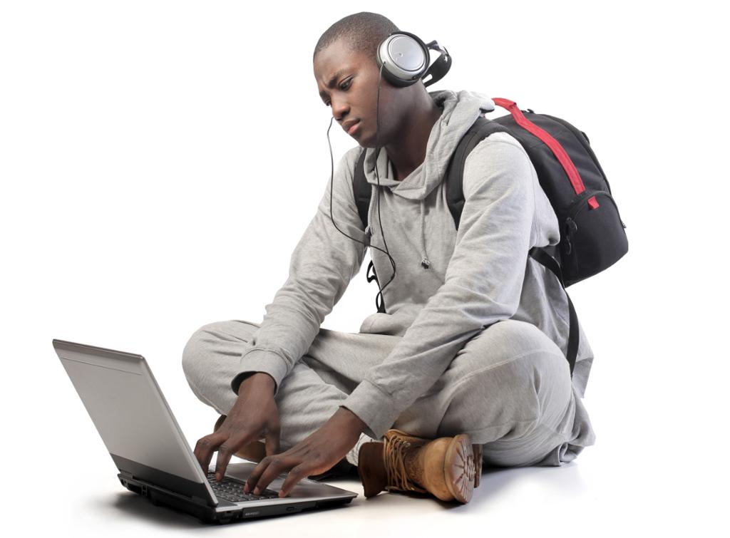 Gutt med skolesekk og hodetelefoner skriver på PC. Foto.