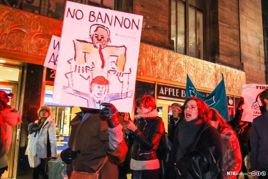 Ungdom protesterer med plakat som viser tegning av to menn. Foto.