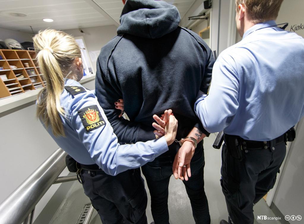 En mann blir ført i arresten av to politibetjenter. Foto.