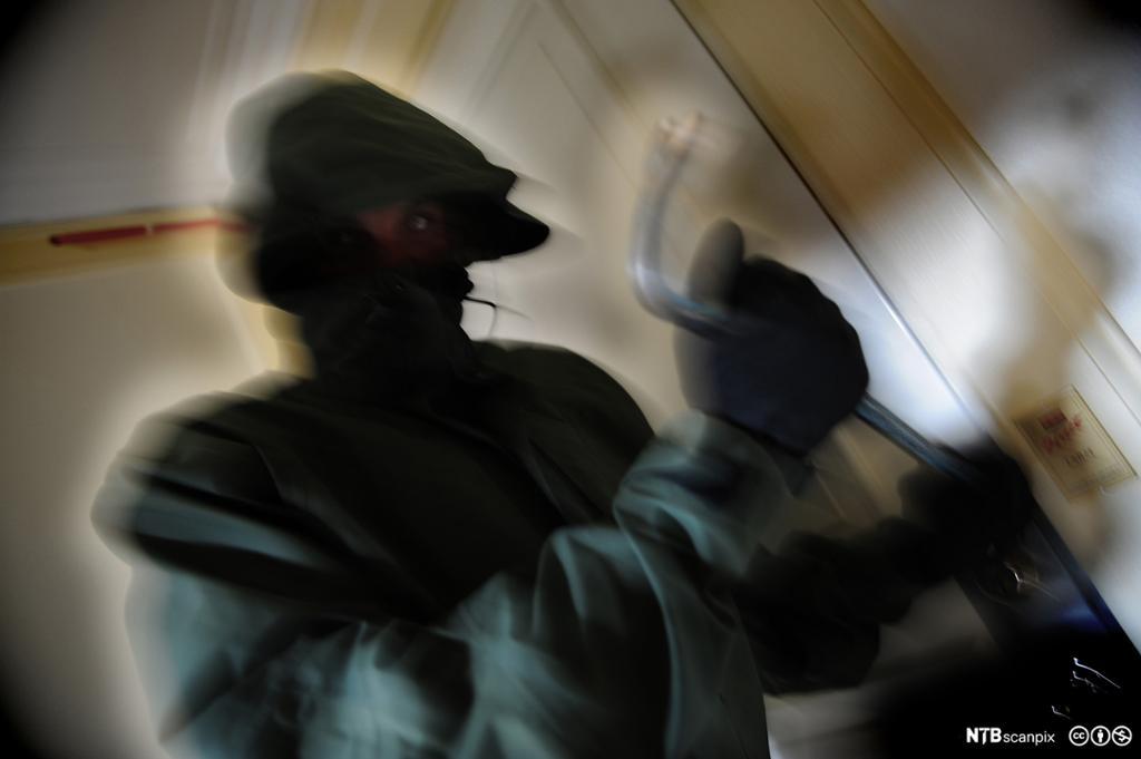 En person gjør innbrudd med brekkjern. Foto.