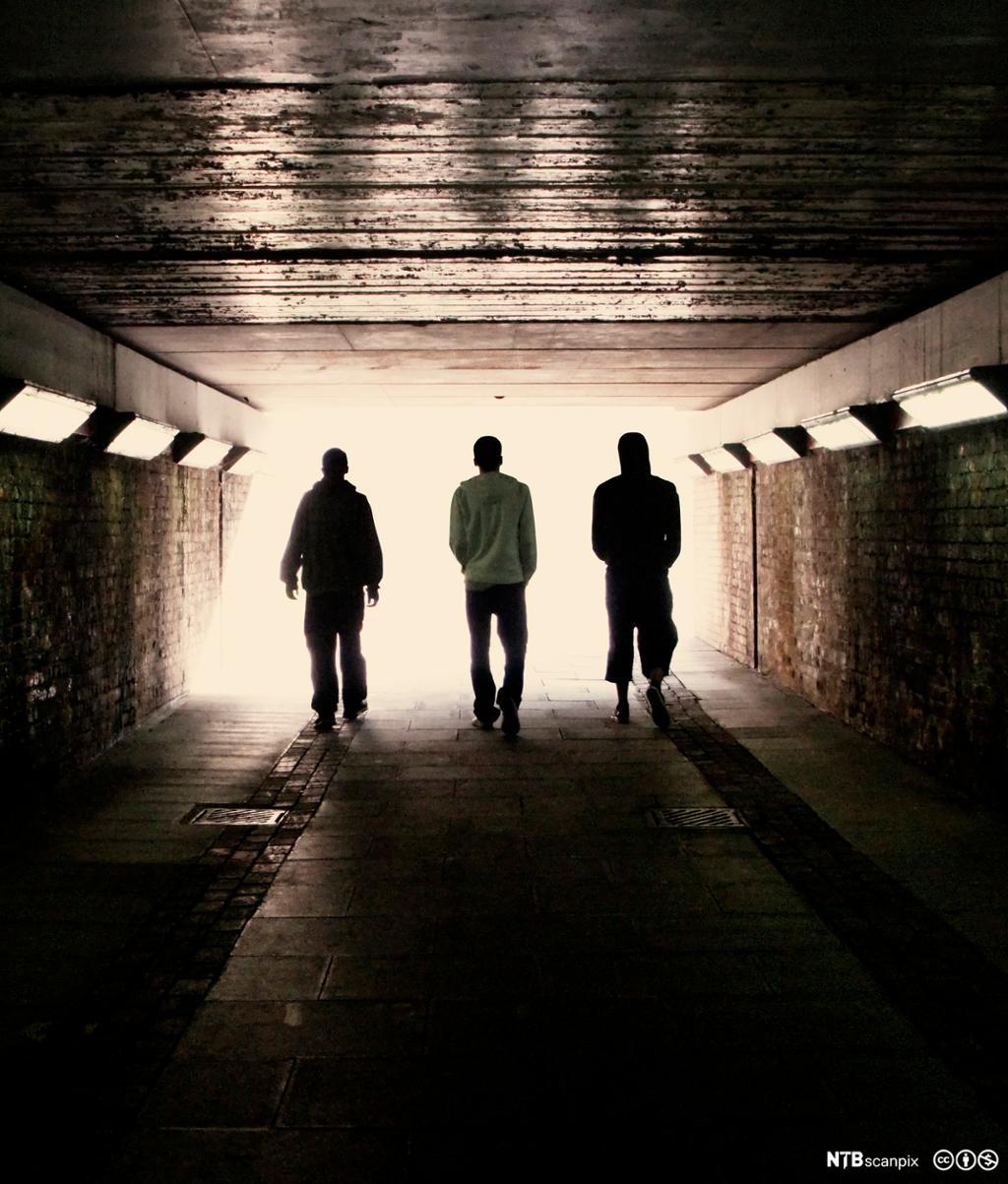 Tre menn går sammen gjennom en undergang. Foto.