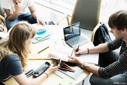 Tre unge personer sitter rundt et bord og arbeider. På bordet er det PC-er, bøker og notatblokker. En noterer, en ser på mobiltelefonen og en leser i en bok. Foto.