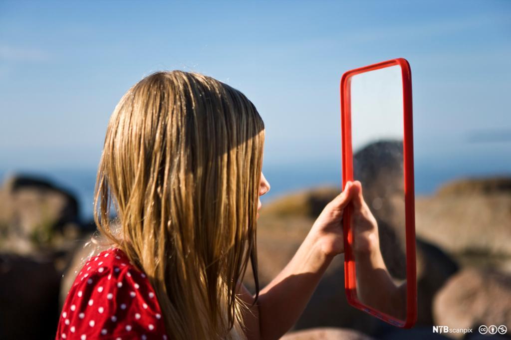 Jente som ser seg i et speil. Foto.
