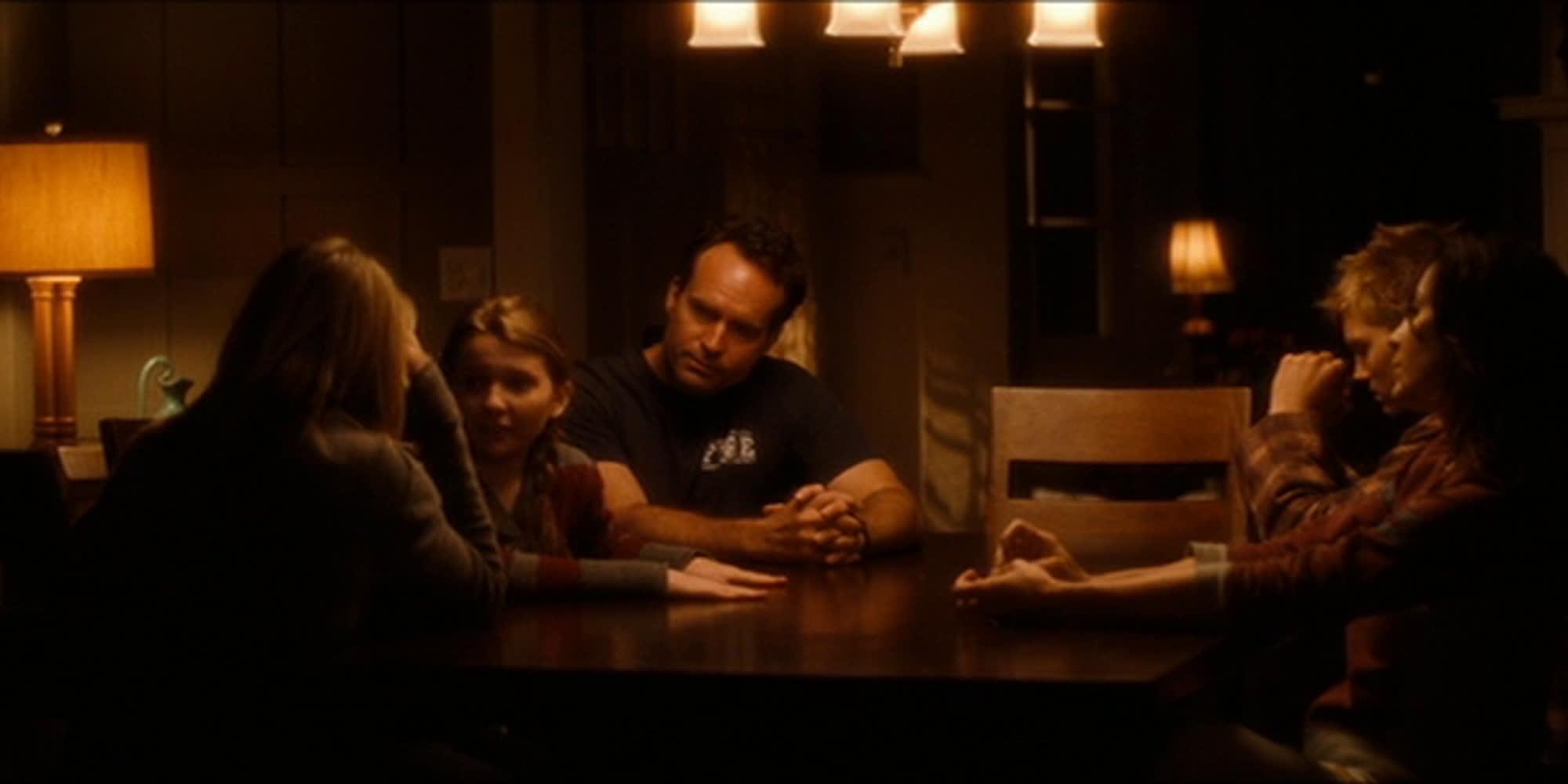 En familie sitter rundt et bord. Belysningen er dempet. Foto.