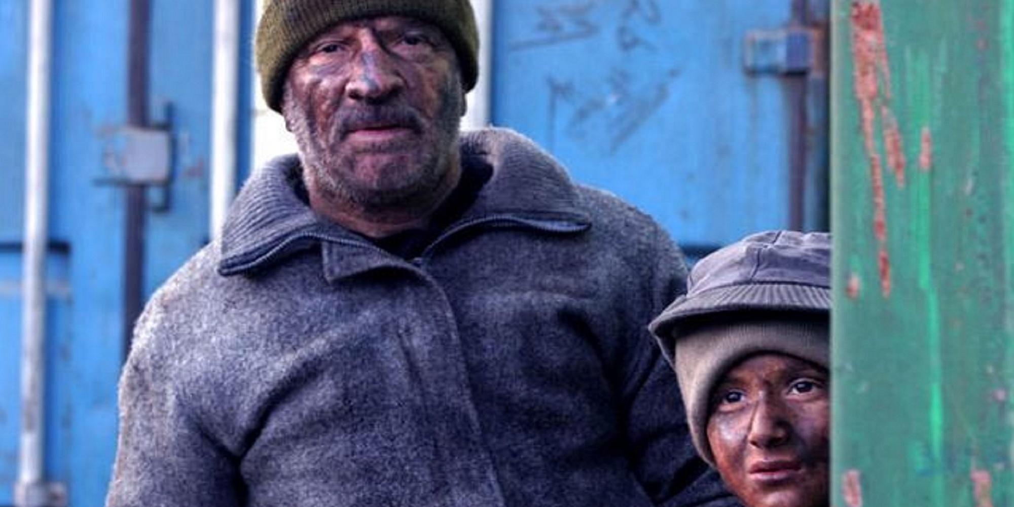 En mann og en gutt som er skitne i ansiktet og på klærne. Utsnitt fra filmen Bawke.