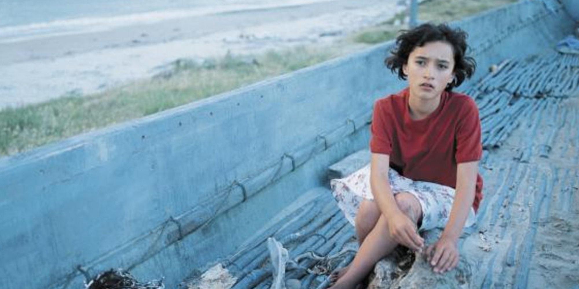 Ung jente med mørkt hår sitter i en gammel båt på en strand. Foto.