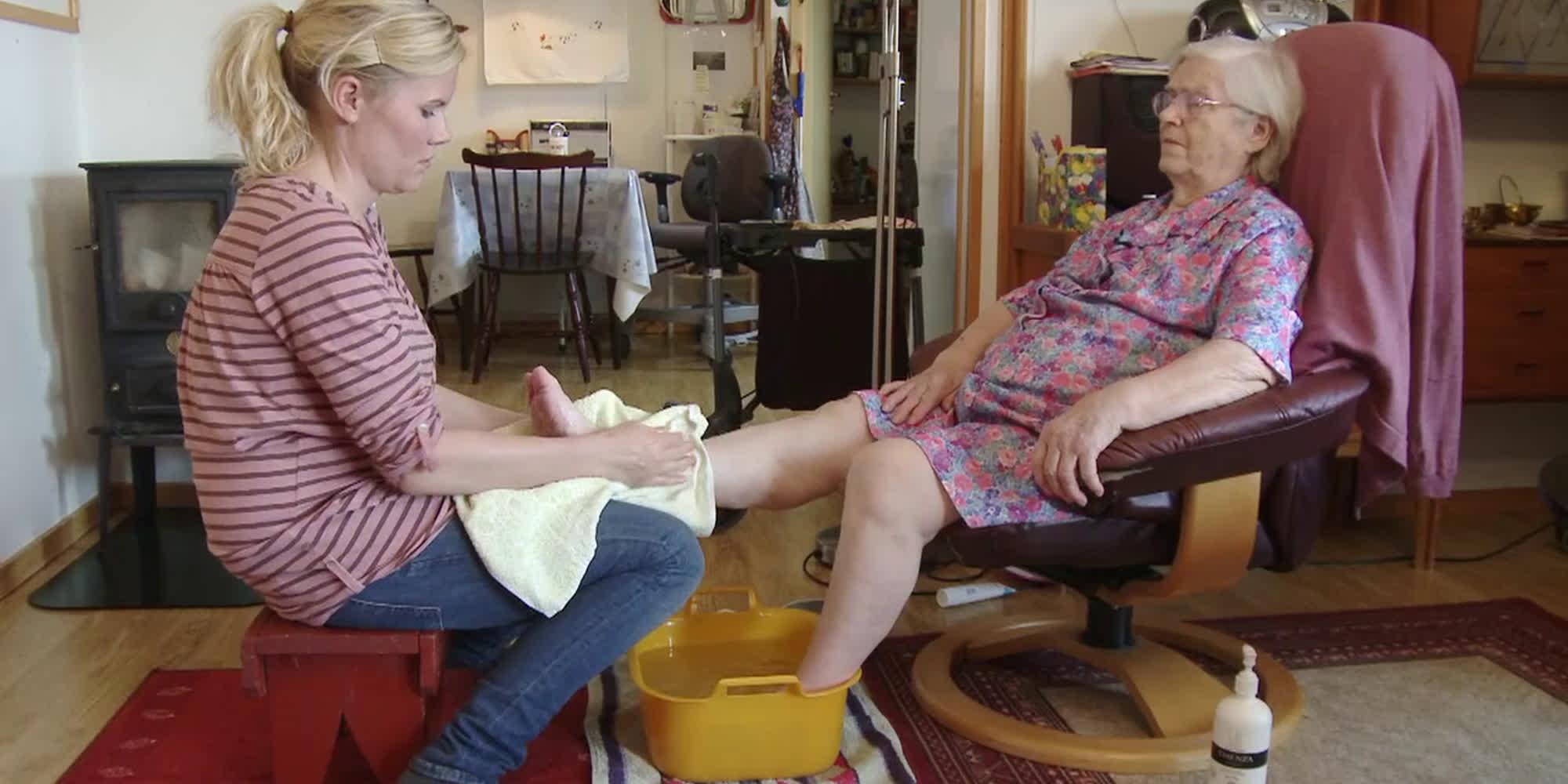 En ung kvinne vasker føttene til en eldre dame i en lenestol. Foto.
