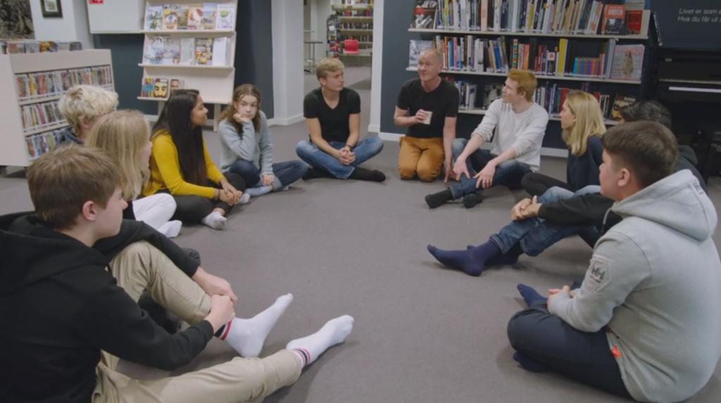 Ungdommer sitter i ring på gulvet og snakker sammen. Foto.