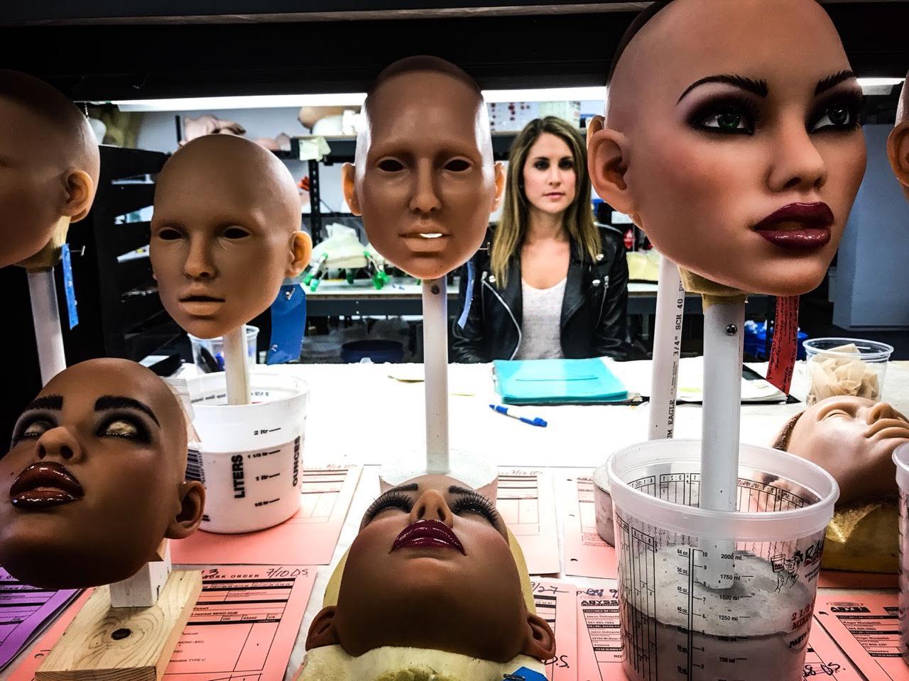 Stativer med syntetiske, menneskelignende ansikter som skal benyttes på roboter. Foto.