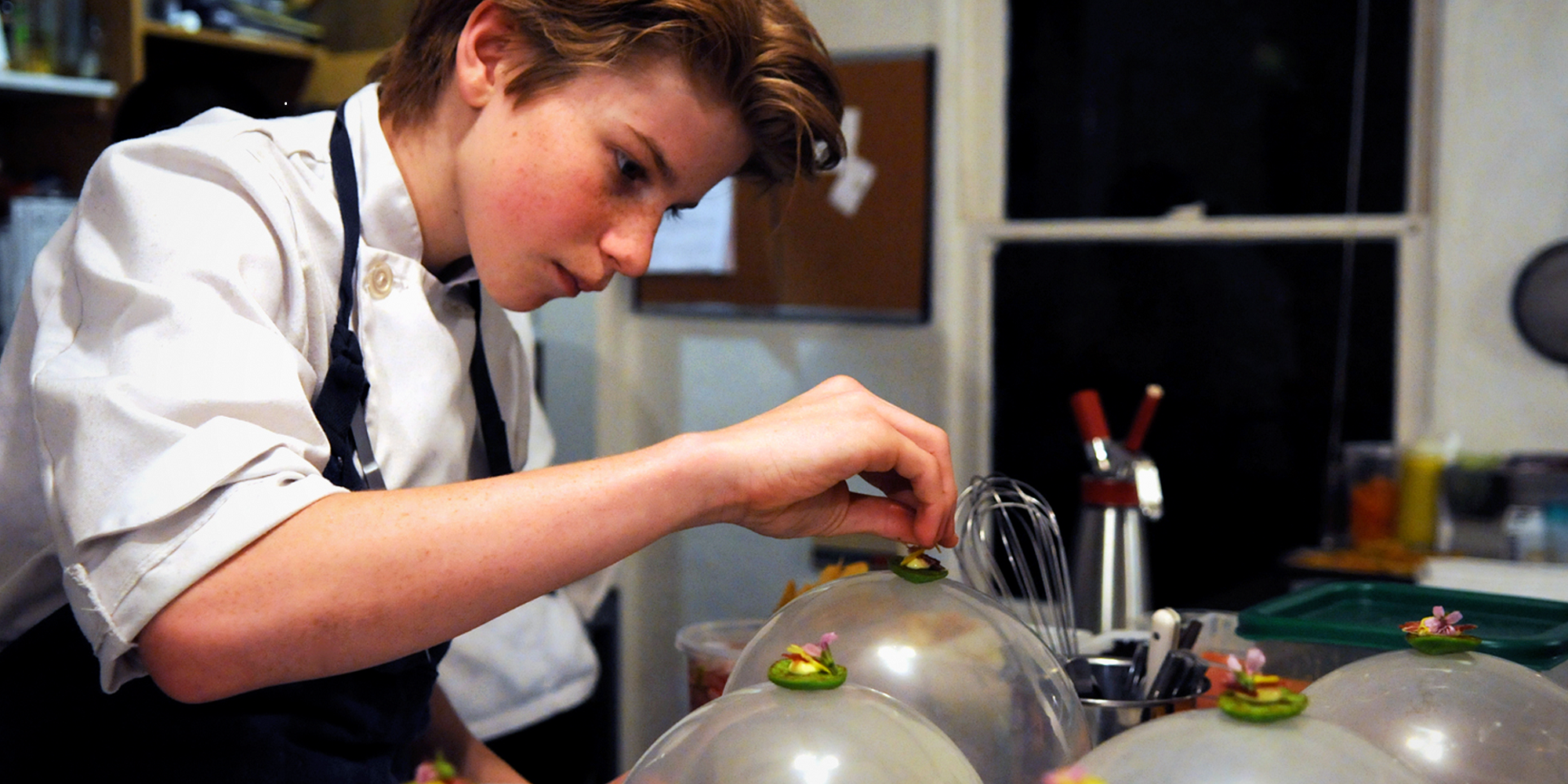Ung gutt i kokkeklær legger mat på fat. Foto.