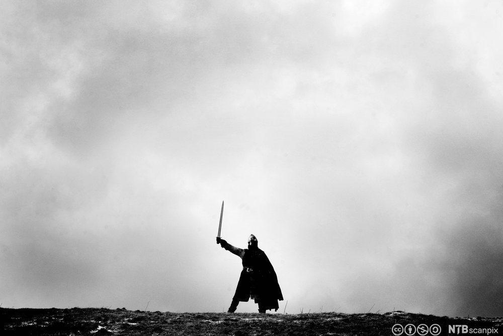 Viking som holder opp et sverd. Foto.