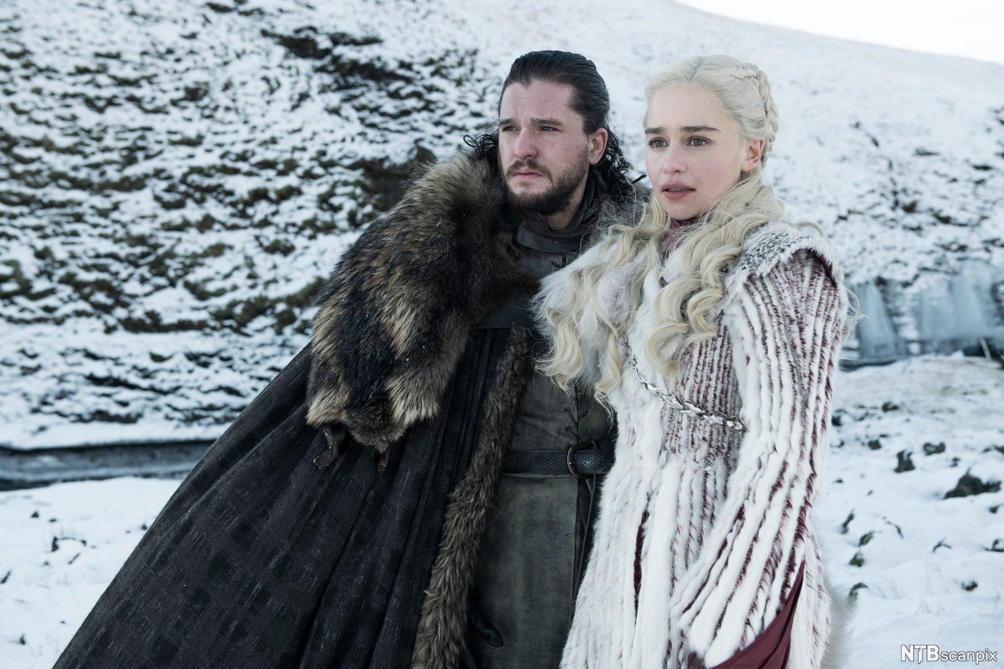 John Snow og Daenerys Targaryen står framfor eit snødekt fjell. Foto.