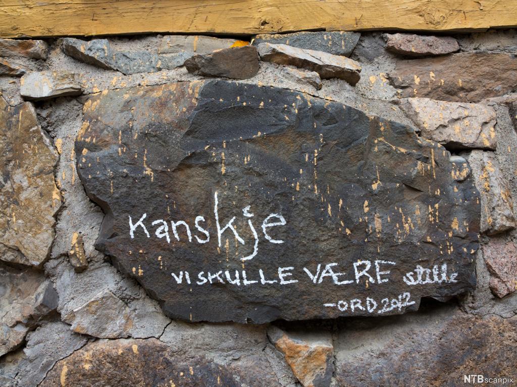 Stein i mur med tekst kanskje vi skulle være stille. Foto