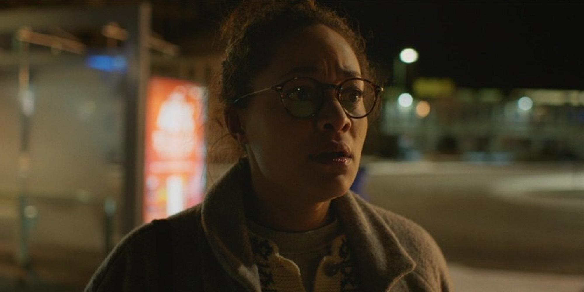 En kvinne med oppsatt hår og runde briller. Hun ser oppskaket ut. I bakgrunnen skimtes en gate nattestid. Foto.