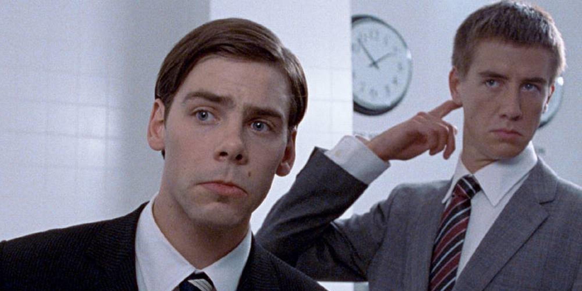 To menn i dress betrakter seg selv i speilet på et herretoalett. Foto.