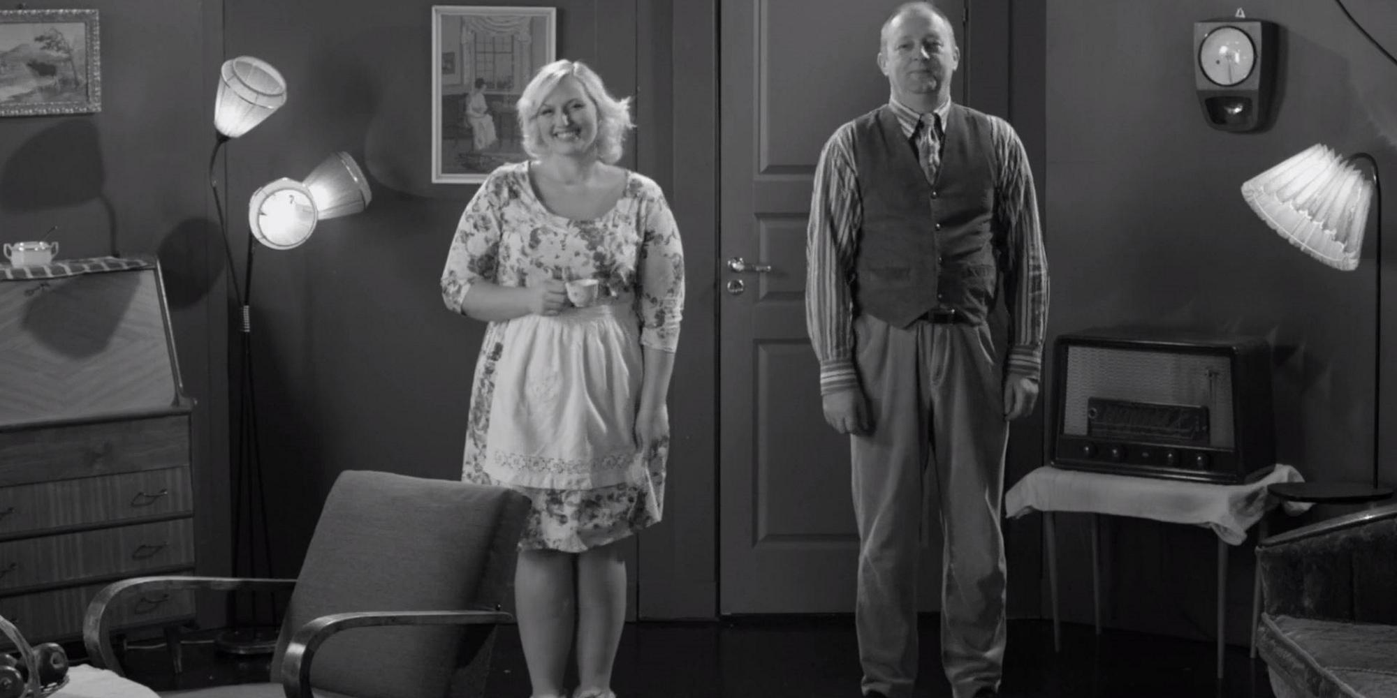Mann og dame smiler mot kameraet. Bildet er i svart-hvitt, og klærne og dekoren er fra 1960-tallet. Foto.
