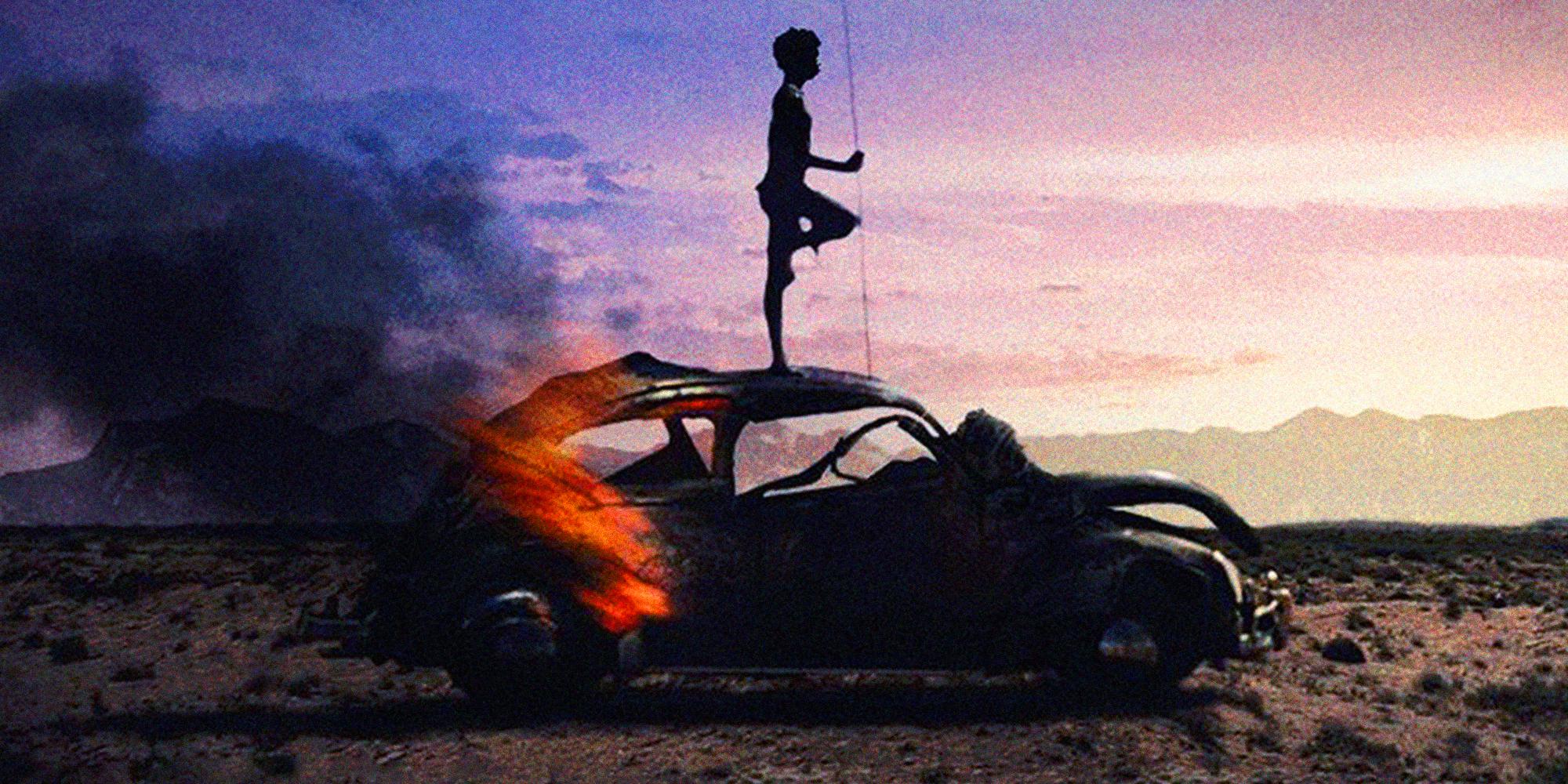 En silhuett av en aboriginer som står på toppen av en utbrent bil i den australske villmarken. Foto.