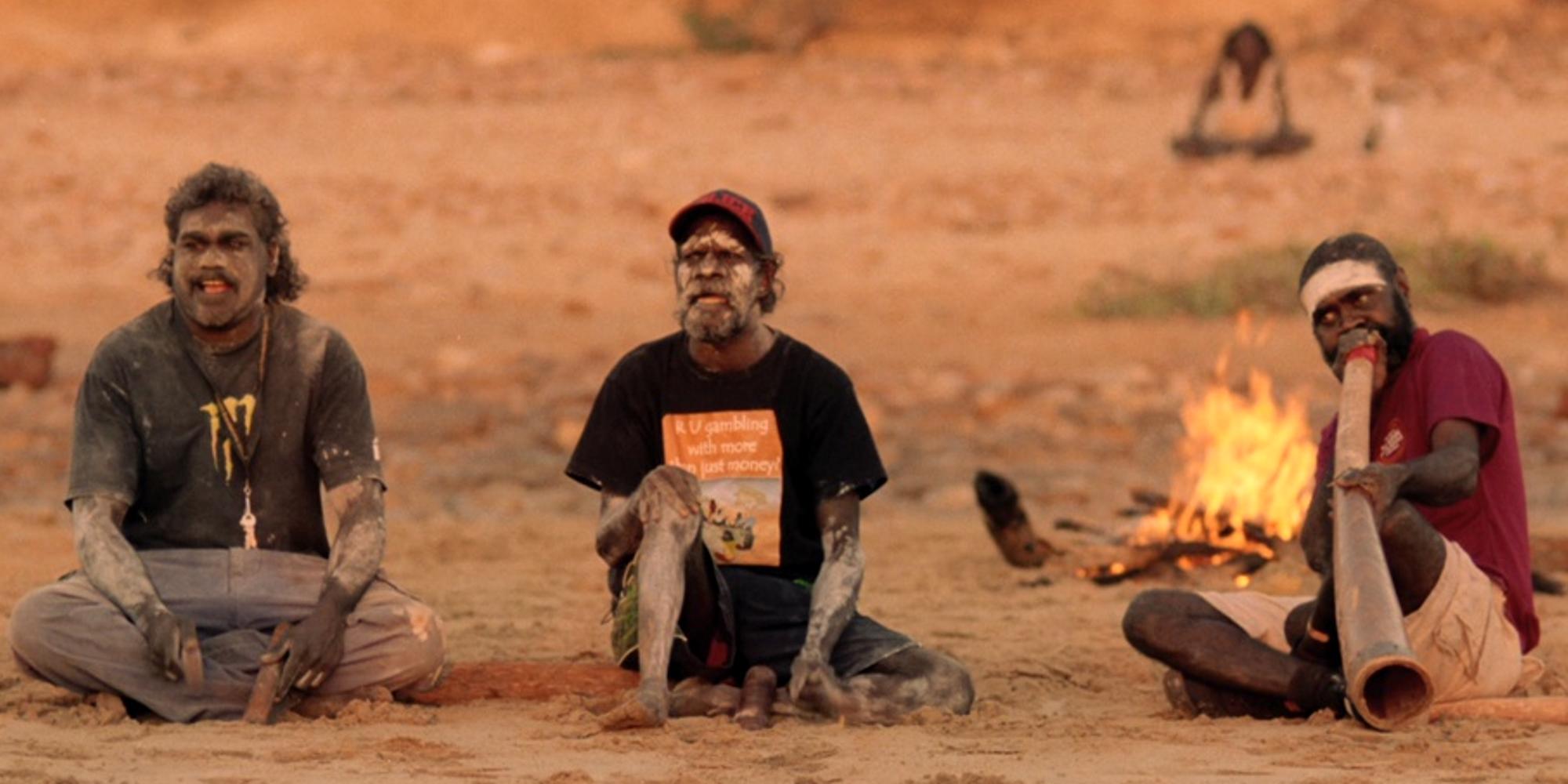 Tre aboriginske menn sitter og spiller tradisjonelle didgeridoo og slaginstrumenter foran et bål i den australske ørkenen. Foto.