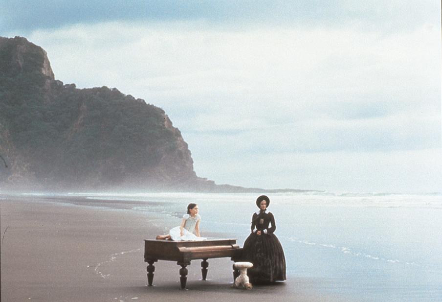 Viktoriansk kvinne i svart kjole og kyse står ved et piano på en strand. Jente i hvitt sitter på pianoet. Foto.