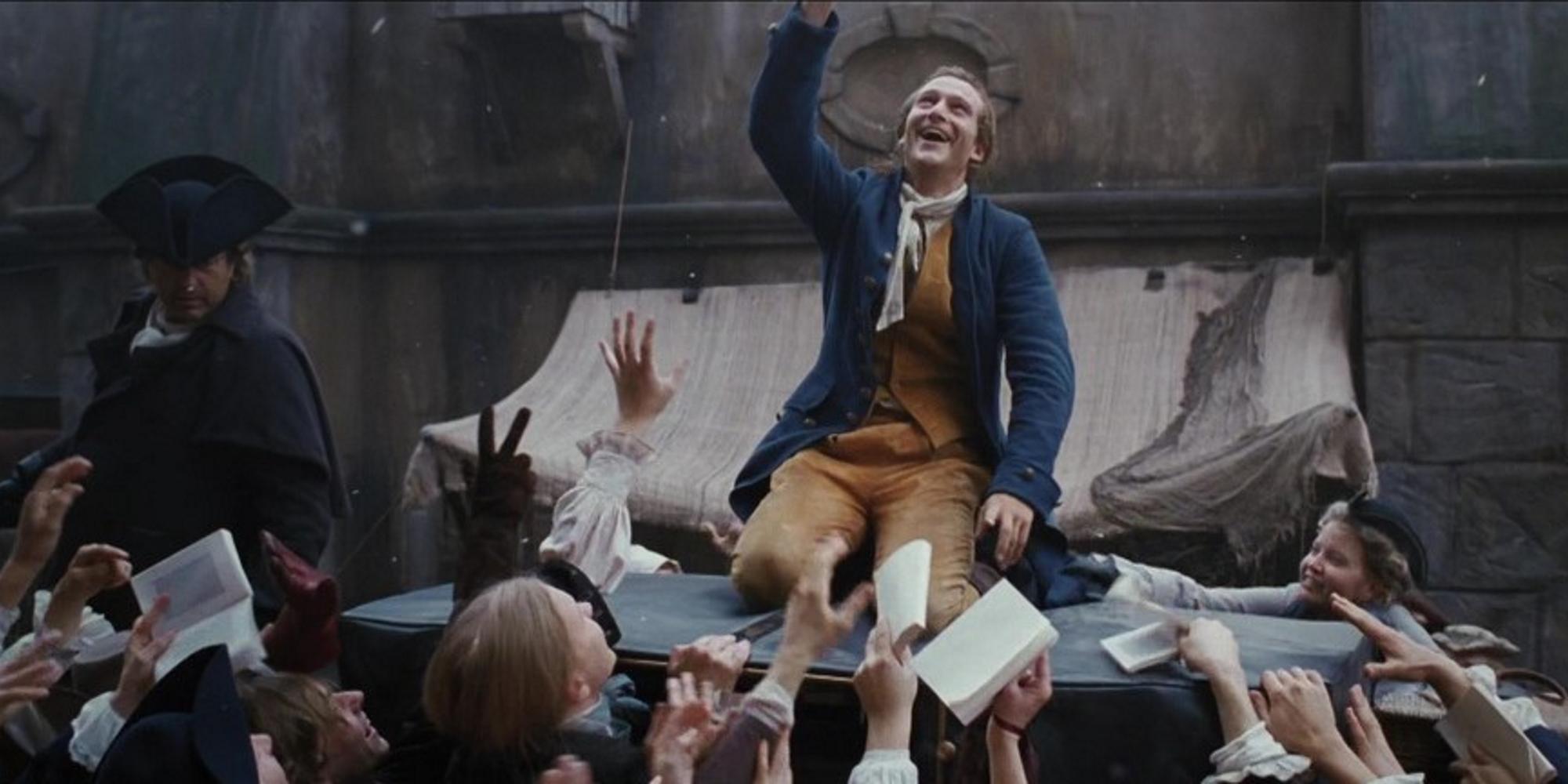 Ung mann ser leende oppover mot himmelen, mens han blir hyllet av en folkemengde. Tidsepoken er andre halvdel av 1700-tallet. Foto.