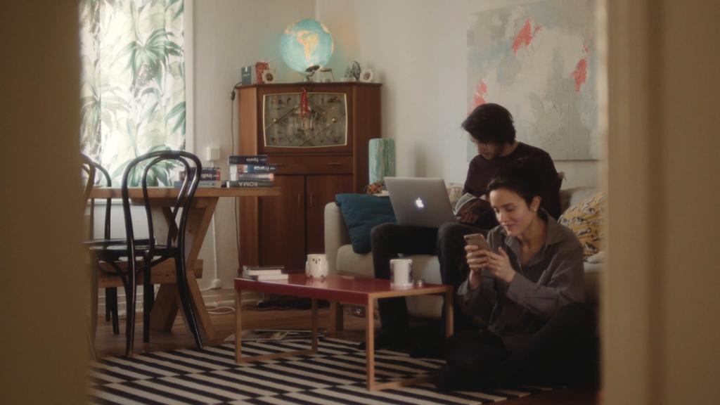 Gutt og jente med pc og mobil sitter i ei stue. Foto.