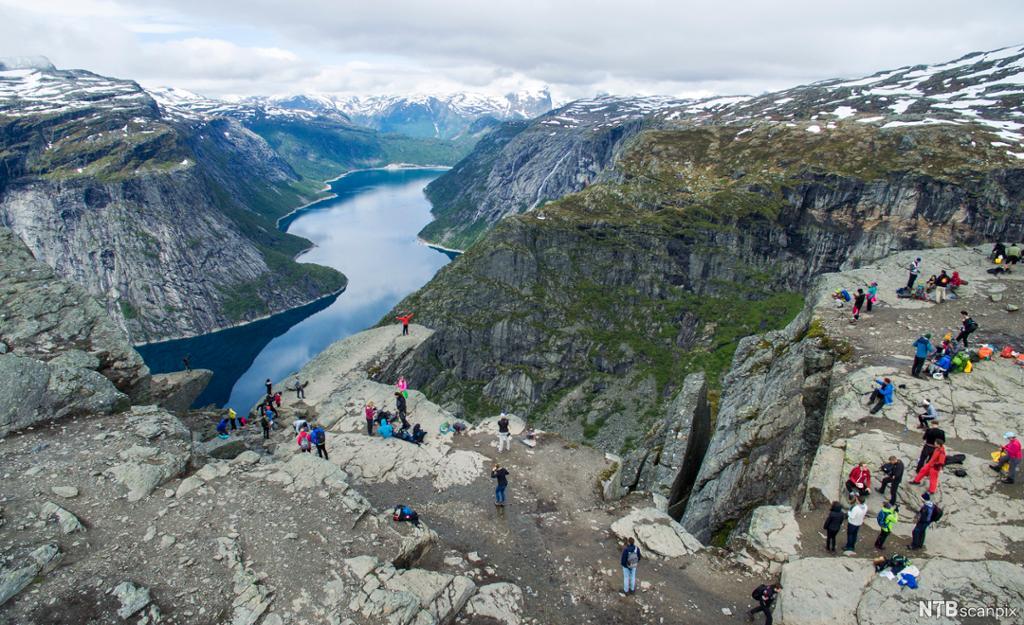 Mange personar på eit fjell. Utsikt til ein fjord og snøkledde fjell. Foto.
