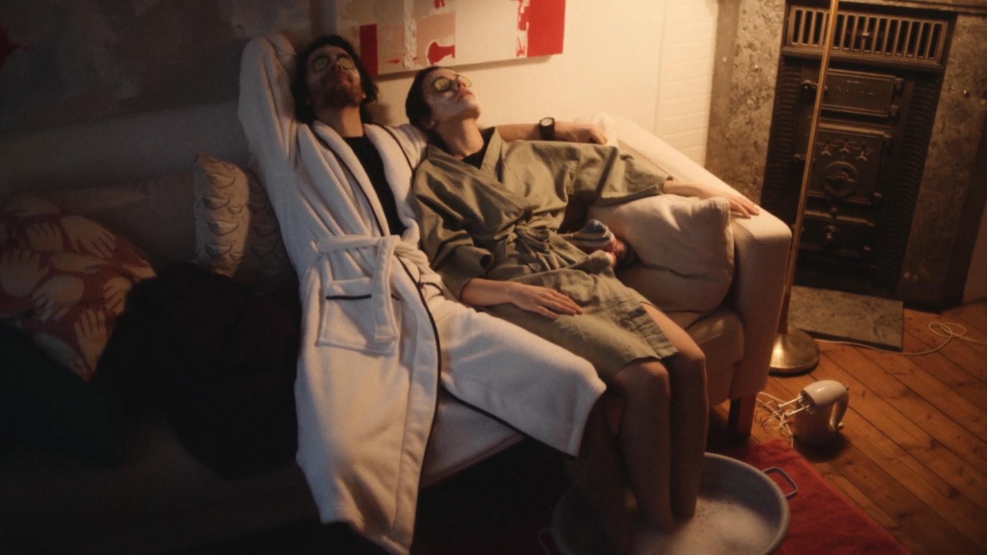 Ungt par iført badekåper ligger utstrakt på sofaen. Foto.