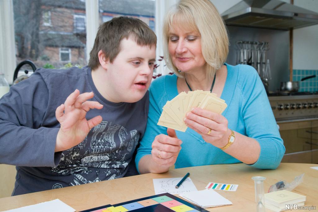 Gutt med Downs syndrom spiller brettspill. Foto.