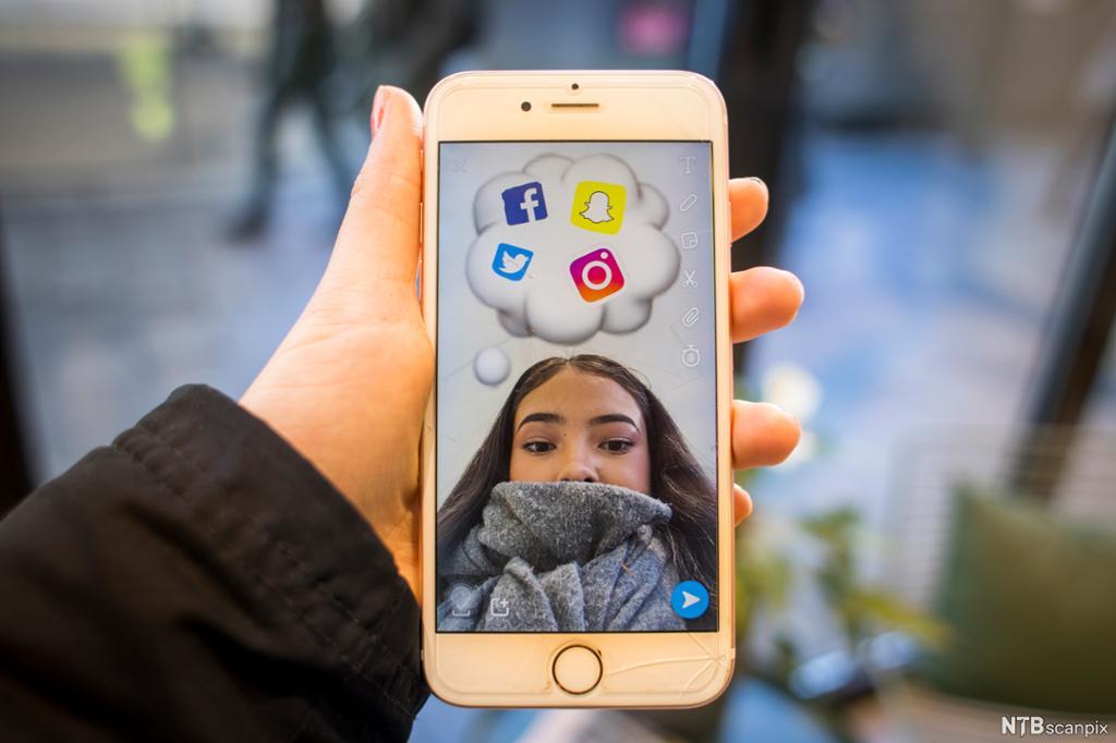 En hånd holder en mobilelefon med et bilde av en jente. Over hodet til jenta er det en snakkeboble med logoer fra flere sosiale medier. Foto.