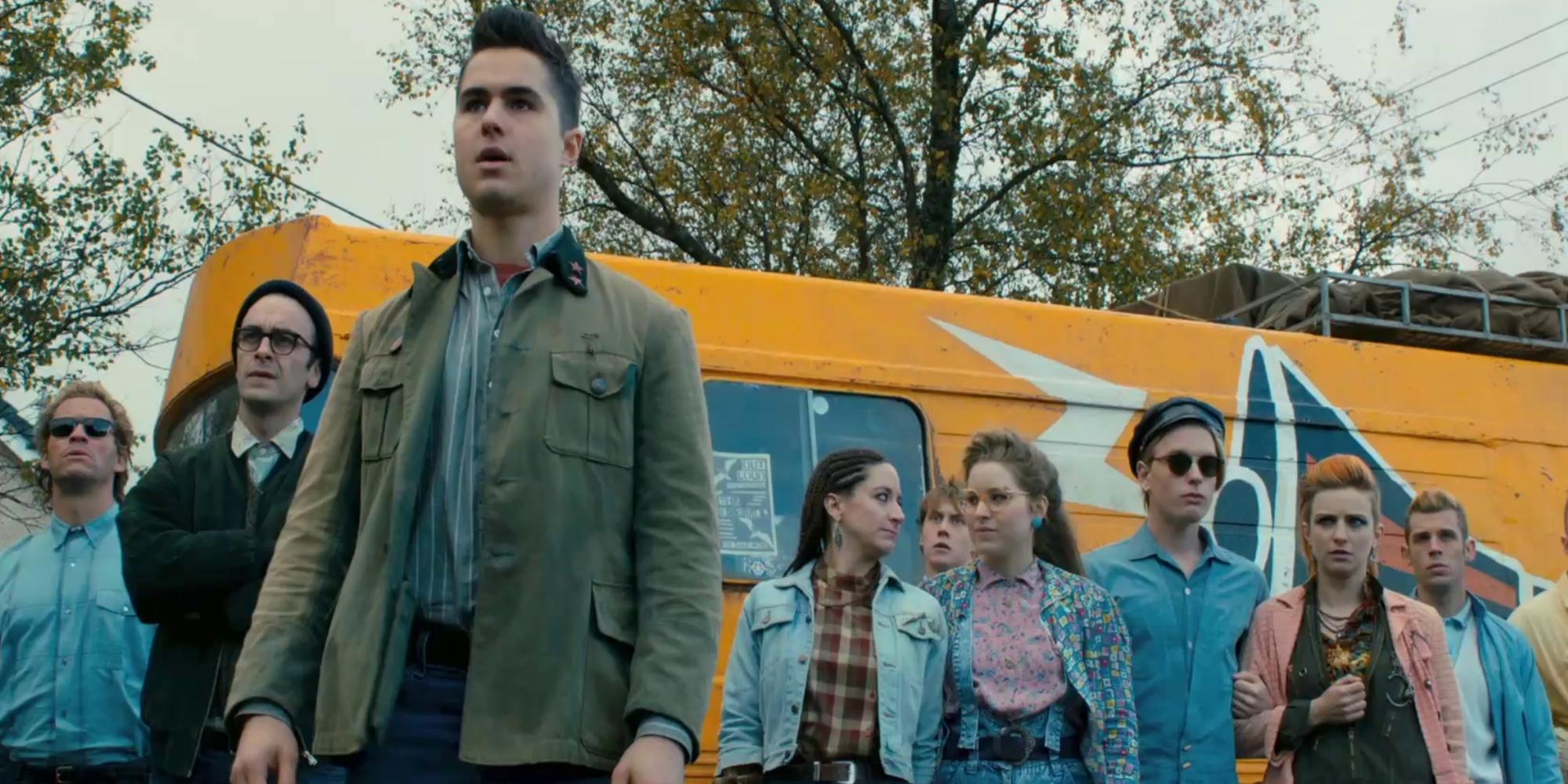 Flere mennesker som er målrettet ut er samlet foran en gul buss. Utsnitt fra filmen Pride.