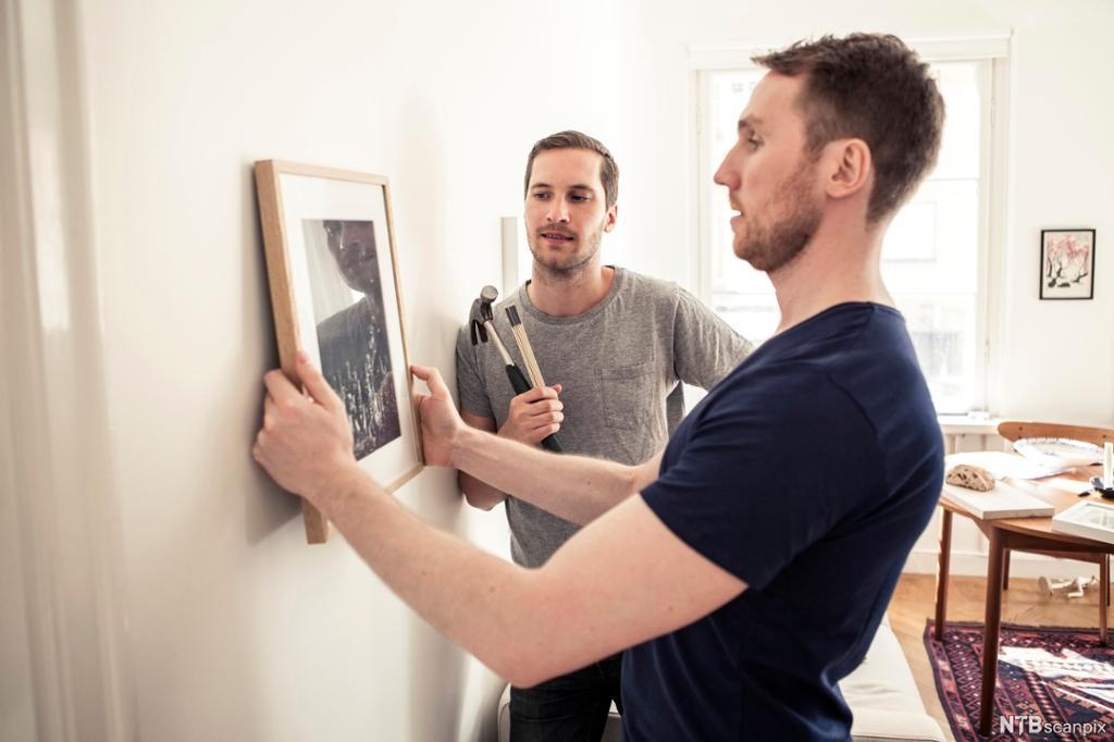 To menn henger opp et bilde på veggen. Foto.