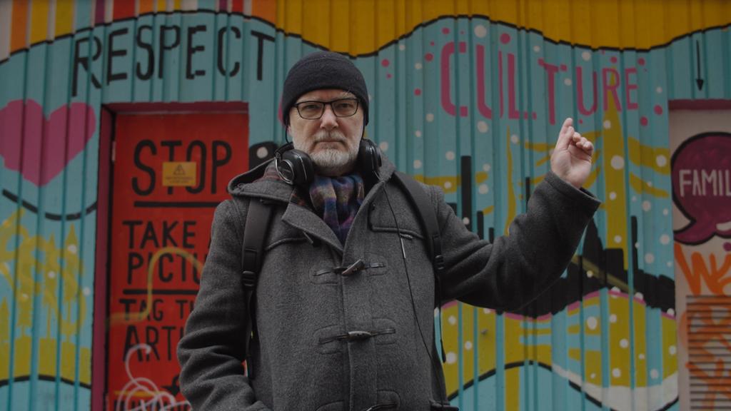 """Forsker Viggo Vestel står foran en vegg med gatekunst og peker på ordet """"culture"""". Foto."""